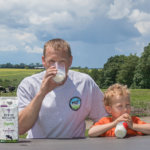 Father and son drinking milk at picnic table with cows and farm in background. Byrne Hollow Farm 1% Low Fat Milk carton on table.
